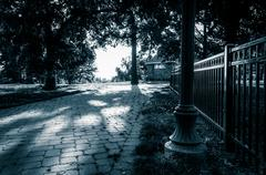 Black and white image of a brick pathway and fence in federal hill park, balt Stock Photos