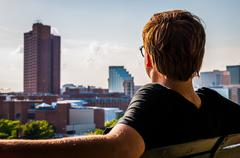 man sitting on bench, looking toward the baltimore skyline from federal hill. - stock photo