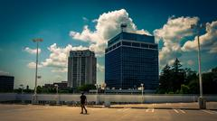 View of highrises and a man walking on a parking garage in towson, maryland. Stock Photos