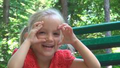 Laughing Playing Child, Funny Little Girl Making Faces Sitting on Bench in Park Stock Footage
