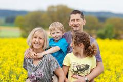 Happy family against flower meadow Stock Photos