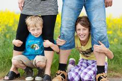 children having fun holding her parents legs - stock photo