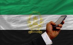 Cell phone in front  national flag of afghanistan Stock Photos