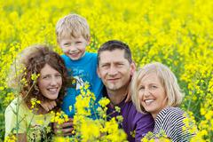 smiling family between rape flowers - stock photo