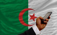 cell phone in front  national flag of algeria - stock photo