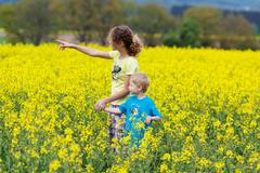 Siblings walking through yellow rape field Stock Photos