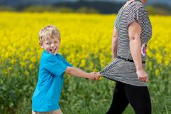 Naughty little boy pulling his mom back Stock Photos