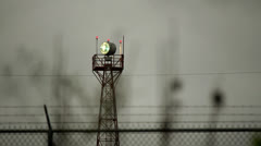 Airport light beacon stormy skies barb wire fence Stock Footage