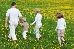 Family walking away over grassy field Stock Photos