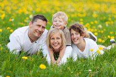 Happy family lying on flower meadow Stock Photos