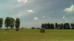 Driving by round hay bales in field on country road Stock Footage