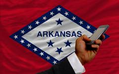 cell phone in front  flag of american state of arkansas - stock photo