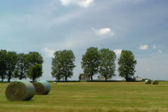 Driving by round hay bales on back country road - stock footage