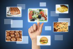 Woman hand uses touch screen interface with food Stock Photos