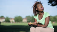 Stock Video Footage of african woman sitting on a log reading a book closer frame