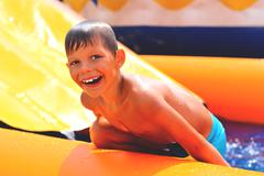 Smiling boy in the water near waterslide Stock Photos