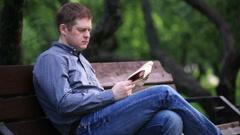 Mies lukee sanomalehteä penkillä puistossa 2 Arkistovideo