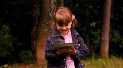 Little girl plays with a tablet, the laptop, the netbook, iPad Stock Footage