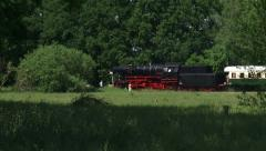 Steam train whistles and passes railway crossing - stock footage