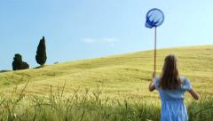 Girl with net is running though field 4K Stock Footage