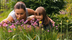 woman and the child smell flowers in a garden - stock footage