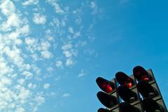Traffic lights against a blue cloudy sky Stock Photos