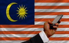 cell phone in front  national flag of malaysia - stock photo