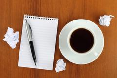Cup of coffee with notepad, pen and crumpled paper . Stock Photos