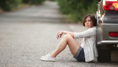 Sad pretty girl sitting on  the road after car accident Stock Footage