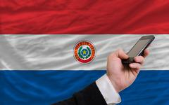 cell phone in front  national flag of paraguay - stock photo
