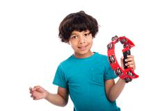 Cute mixed race kid with tambourine. Stock Photos