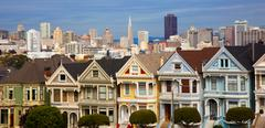 Famous row houses in san francisco ca. with skyline behind Stock Photos