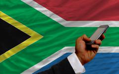 cell phone in front  national flag of south africa - stock photo