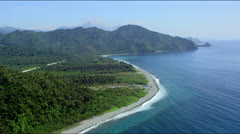 coast line with beach, forest towards forest covered mountain range - stock footage