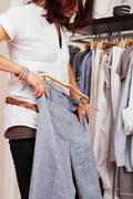 Woman trying trouser in clothing store Stock Photos