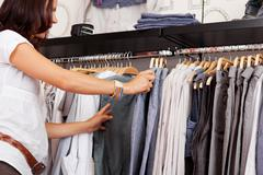 Woman choosing trouser from rack in clothing store Stock Photos