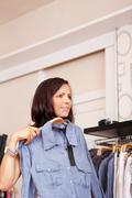 Woman trying shirt while looking away in clothing store Stock Photos