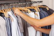 Stock Photo of choosing shirt from rack in clothing store