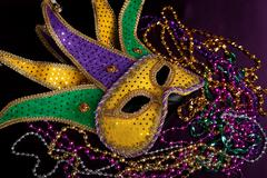A mardi gras jester's mask with beads on a black background Stock Photos