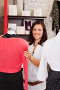 Woman examining clothes on mannequin in clothing store Stock Photos
