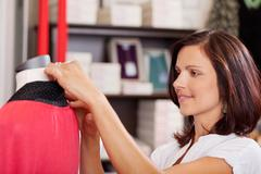 Saleswoman examining clothes on mannequin Stock Photos