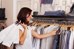 Customer choosing clothes from rack in clothing store Stock Photos