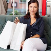 Woman with shopping bags sitting on sofa at clothing store Stock Photos