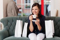 Customer drinking coffee while sitting on sofa at clothing store Stock Photos