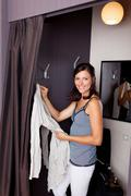 Woman looking in camera while standing in changing room Stock Photos