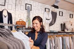 Customer looking at shirt in clothing store Stock Photos