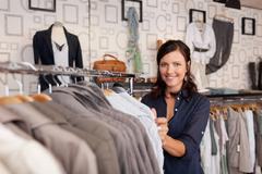 smiling woman choosing shirt in clothing store - stock photo