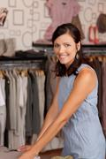 Female customer choosing clothes at desk in boutique Stock Photos