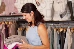 saleswomen holding stack of clothes in boutique - stock photo