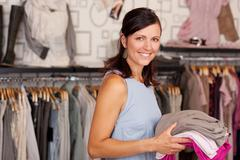 Smiling woman holding stack of clothes in boutique Stock Photos